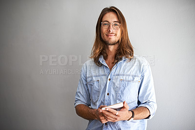 Buy stock photo Studio portrait of a young man using a digital tablet against a gray background