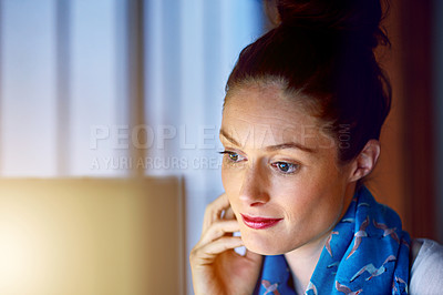 Buy stock photo Shot of a young woman working on her computer in an office late in the evening