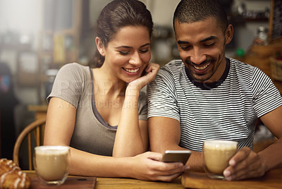 Buy stock photo Shot of a young couple using a cellphone while sitting in a coffee shop