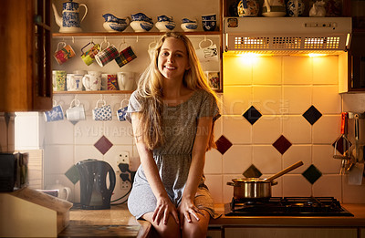 Buy stock photo Portrait of an attractive young woman sitting in her kitchen