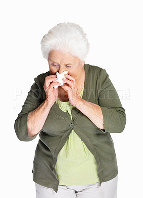 Buy stock photo Portrait of an allergic senior woman using a tissue paper isolated against white