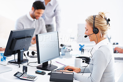 Buy stock photo Friendly customer service representative at her computer wearing headset with colleagues in background