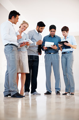 Buy stock photo Full length of business people standing together at corridor while busy discussing paperwork
