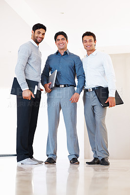 Buy stock photo Full length of smiling business men standing together in office corridor