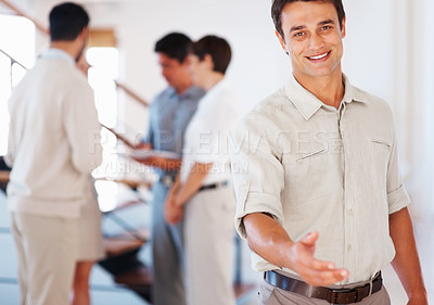 Buy stock photo Business man giving you handshake with colleagues discussing in background