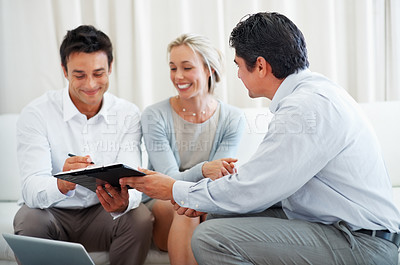 Buy stock photo Business consultant presenting new investment plans to couple for signing