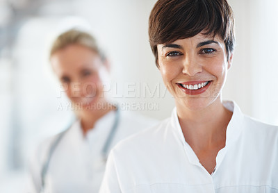 Buy stock photo Portrait of female doctor smiling with colleague in background