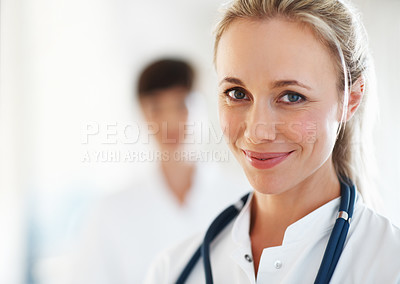 Buy stock photo Closeup of female doctor giving you cute smile with colleague in background