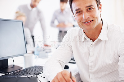 Buy stock photo Portrait of handsome business man sitting at his desk with colleagues in background