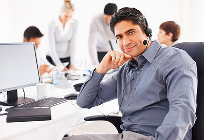 Buy stock photo Confident customer executive sitting in front of computer with colleagues in background