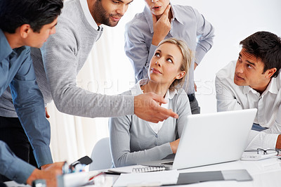 Buy stock photo Male executive presenting something on laptop to his business colleagues