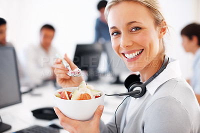Buy stock photo Closeup of female customer executive eating bowl of fruit salad with colleagues in background