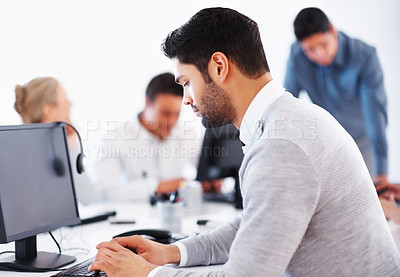 Buy stock photo Business man working on computer with colleagues in background