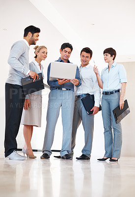 Buy stock photo Full length of male leader with his team working on laptop in the corridor
