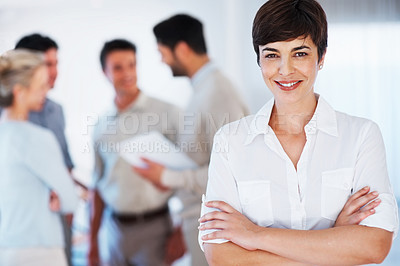 Buy stock photo Short haired business woman with hands folded and colleagues discussing in background
