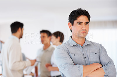 Buy stock photo Serious business man with hands folded and colleagues discussing in background