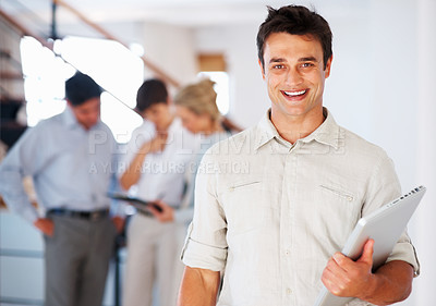 Buy stock photo Portrait of smiling business man holding laptop and looking at you with colleagues in background