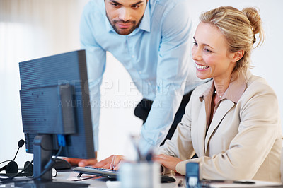 Buy stock photo Business woman working on computer with male executive assisting her