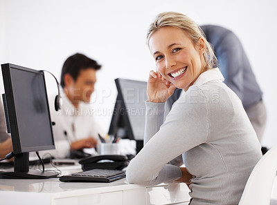 Buy stock photo Smiling customer care representative sitting in front of computer with colleagues in background