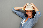 Happy cowgirl holding her hat