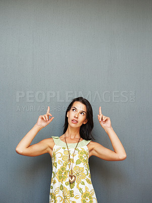 Buy stock photo Woman making uncertain face and pointing up