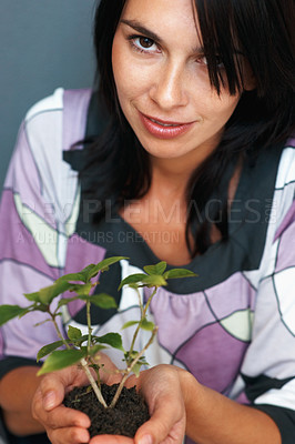 Buy stock photo Woman smiling while holding live plant in her hand