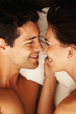 Buy stock photo Closeup portrait of romantic young couple lying in bed