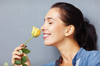 Buy stock photo Side view of pretty woman smelling yellow rose