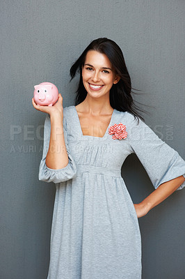 Buy stock photo Smiling young woman holding piggy bank in hand