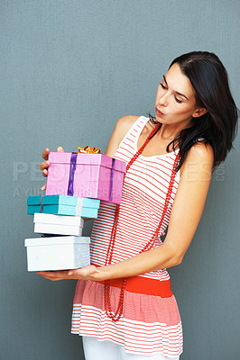 Buy stock photo Portrait of pretty young woman holding a pile gifts against a grey background