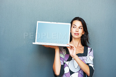 Buy stock photo Portrait of pretty young woman glancing at laptop