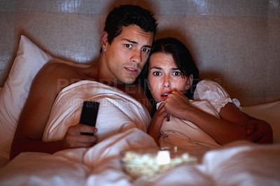 Buy stock photo Portrait of young couple watching horror movie while lying on bed