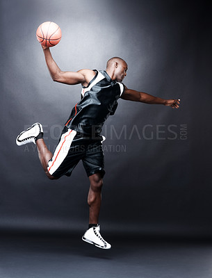 Buy stock photo Portrait of a young black guy playing basketball on dark background