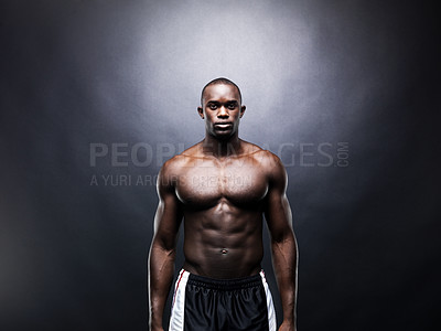 Buy stock photo Portrait of a young Afroamerican guy standing shirtless against dark background