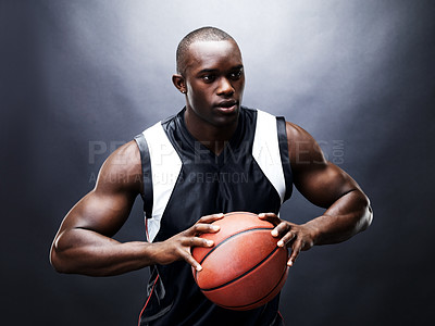 Buy stock photo Portrait of a young black guy in action with basketball against black background