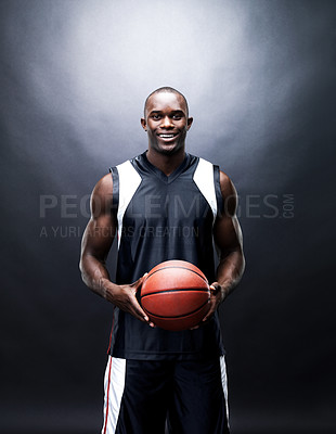 Buy stock photo Portrait of a happy young man holding a basketball against grunge background