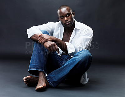 Buy stock photo Portrait of an afroamerican young man siiting relaxed on floor against grunge background