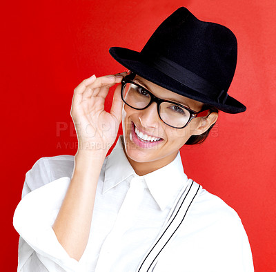 Buy stock photo Portrait of a happy young woman in glasses and hat against red background