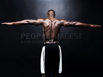 Buy stock photo Portrait of a strong back of a black muscular man streching his arm against dark background