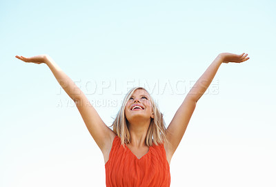 Buy stock photo Happy young woman with arms raised looking at the sky