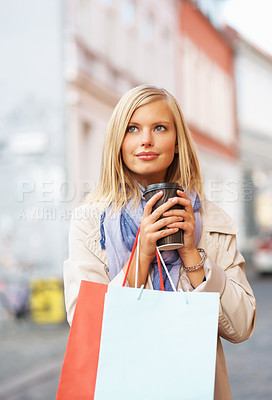 Buy stock photo Pretty young woman enjoying a takeaway coffee while out shopping - copyspace