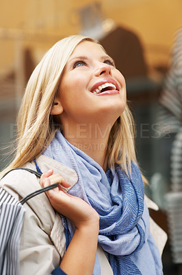 Buy stock photo Urban woman with shopping bag looking up