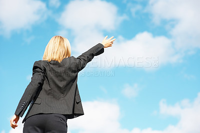 Buy stock photo Rear view of business woman pointing towards the blue sky