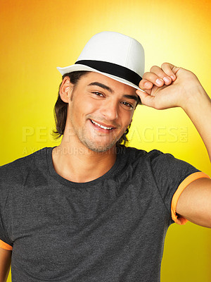 Buy stock photo Handsome man against yellow background holding brim of hat