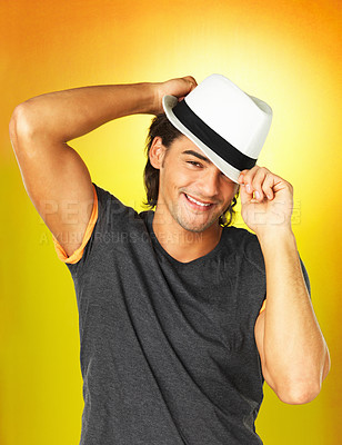 Buy stock photo Handsome young man tilting his hat at you while against an orange, flared background