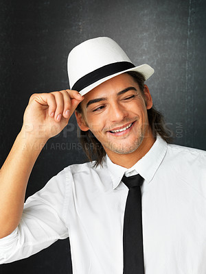 Buy stock photo Flirtatious man against gray background holding brim of hat while winking