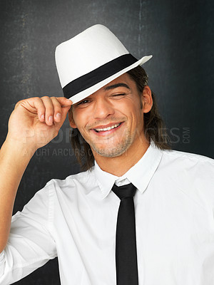 Buy stock photo Handsome man against gray background holding brim of hat while winking