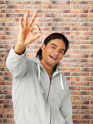 Buy stock photo Man standing against brick wall giving ok sign