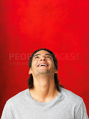 Buy stock photo Handsome man looking up and smiling against red background