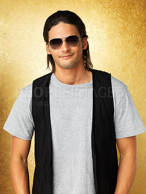 Buy stock photo Handsome man smiling while wearing sunglasses against gold background